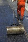 Worker using a hand roller for mastic asphalt paving poster