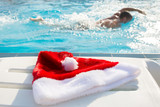 Fototapety Christmas hat by the swimmingpool on a sunny day