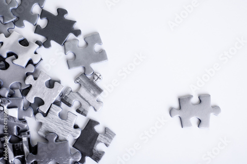 Jigsaw shot on a white background from above with one piece standing out