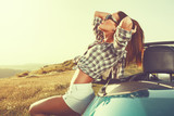 Attractive young woman posing leaning on convertible car at suns