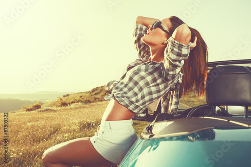 Fototapeta Attractive young woman posing leaning on convertible car at suns