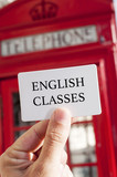 Fototapety text english classes in a signboard and a red telephone booth in