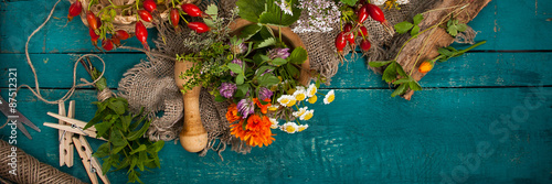 Summer fresh medicinal herbs on the wooden background.