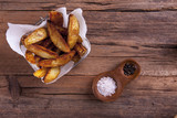 Wedges shot on a wooden background from above with salt and pepper and in a basket on cooking or greaseproof paper