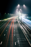 Traffic light trails. Long exposure of a UK motorway at night time with traffic trails illustrating cars driving on the left.