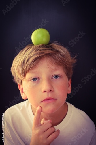 Poster Thinking child with an apple balancing on his head