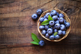 Fresh ripe garden blueberries in a wicker bowl on dark rustic wooden table. with copy space for your text - 87630551