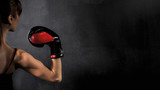 Woman Boxer Biceps with Red Boxing Glove on Black Background, high contrast with saturated grunge filter - 87661706