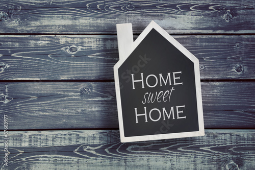 House shaped chalkboard on wooden background Photo by Sandra Cunningham