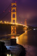 The famous San Francisco Golden Gate Bridge in California, United States of America. A long exposure of Fort Point, the bay and the illuminated red suspended bridge at night looking as if on fire.