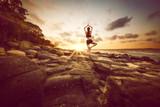 Fototapety Woman meditates on rocks by the beach