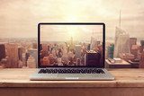 Laptop computer over New York city skyline. Retro filter effect - Fine Art prints