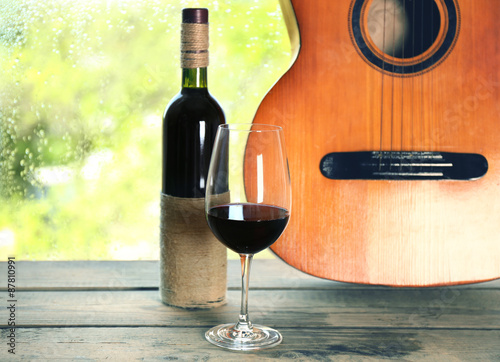 Fototapeta Acoustic guitar and glass of wine next the window with rain drops