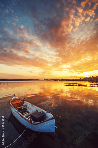 Beautiful sunset over calm lake and a boat with sky reflecting i