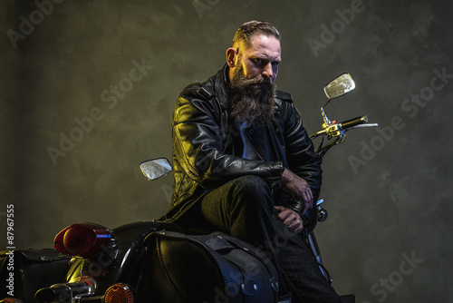 Serious Bearded Biker Man Sitting on a Motorcycle