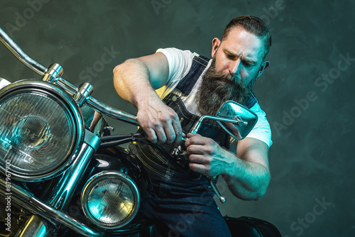 Man Sitting on his Motorcycle and Fixing Something Poster