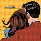 Fototapety Loving couple looking at a plane taking off in the sky