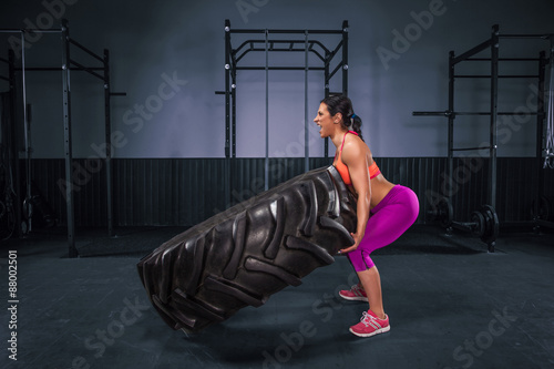 Poster Fit and beauty strong girl exercise with big tire.
