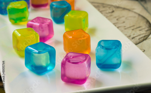 horizontal image of colourful plastic water filled ice cubes sitting on a white plate.  © nat2851terry