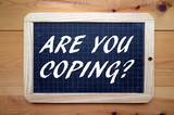 The question Are You Coping? in white text on a slate blackboard