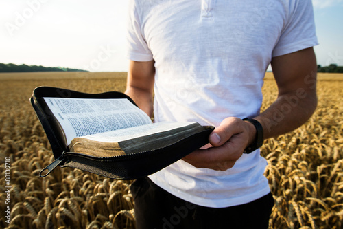 Zdjęcia na płótnie, fototapety, obrazy : Man holding open Bible in a wheat field