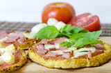Fototapety Close up of small round baked cauliflower crust pizzas topped with bacon,ham,halloumi,cottage cheese,lountza,pineapple,turkey,tomato sauce, basil on a wooden chopping board.Healthy pizza snack