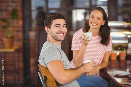 Smiling friends sitting and drinking coffee