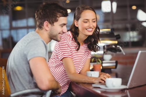 Smiling friends using laptop and having coffee together