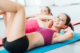 Fototapety Smiling women exercising at the gym