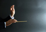 Fototapety Music conductor hands with baton on black background