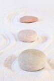 Zen stones on white sand, conceptual image, vertical composition.