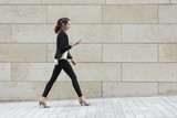 Fototapety Businesswoman looking at phone while walking.