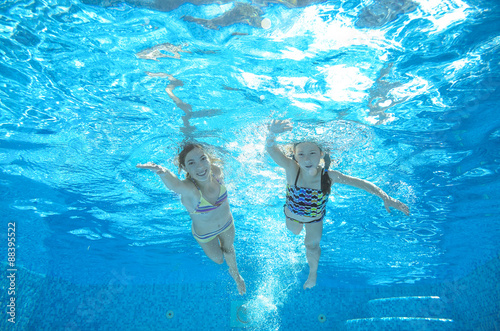 Poster Children swim in pool underwater, happy active girls have fun in water