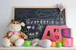 Постер, плакат: A blackboard in a kindergarten classroom Some baby stuff Foam letters cubes and hand made drawings The word GUARDERIA Spanish word that means KINDERGARTEN