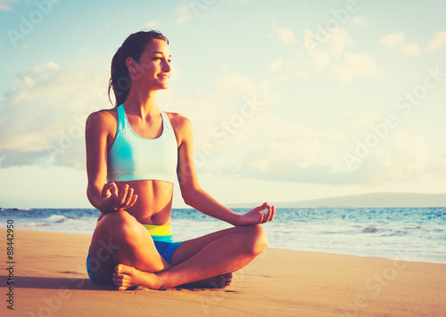 Woman Practicing Yoga on the Beach at Sunset плакат