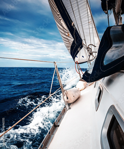 Fototapeta The white sails of yachts on the background of sea and sky in the clouds