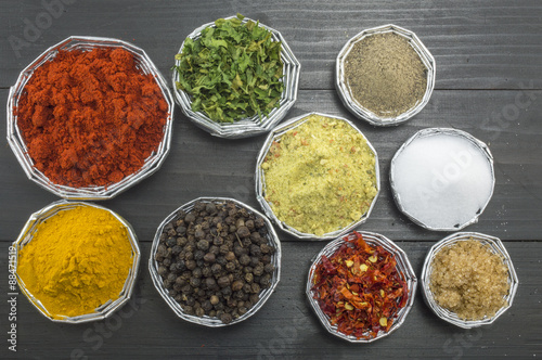 Poster Different spices in shiny bowls on a dark wooden table