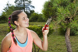Pretty smiling young woman with cute freckles, cutting and pruning a big bonsai pine tree, on a lovely sunny summer day