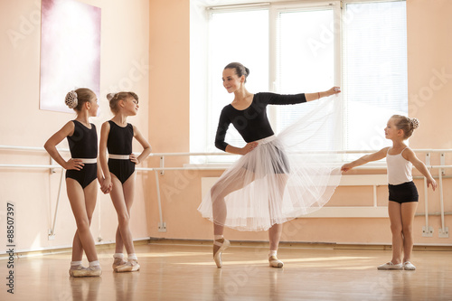 Plagát Young girl warming up and talking to younger classmates at ballet dancing class