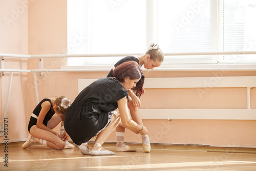 Ballet teacher helping young students to prepare for pointe-work © Andrey Bandurenko
