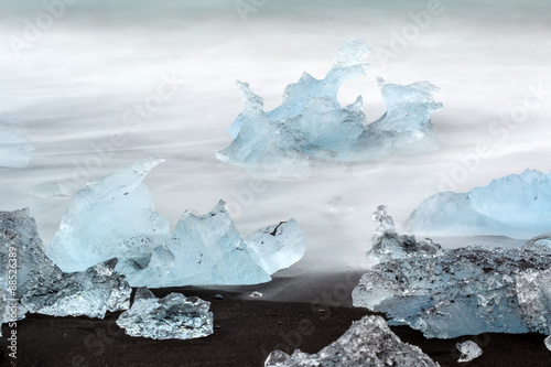 Plakat black lava sand with icebergs from glaciers