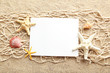 Empty blank of sheet paper on beach sand with sea shells