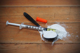 Drug syringe and heroin powder on spoon