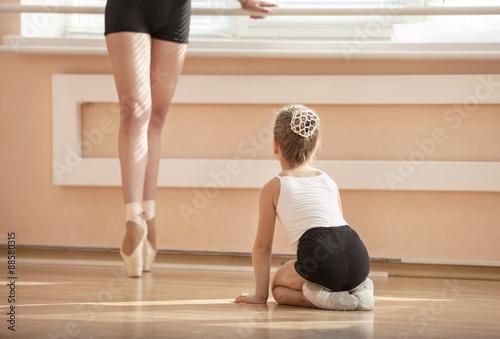 Girl beginner watching classmate standing en pointe in ballet dancing class © Andrey Bandurenko