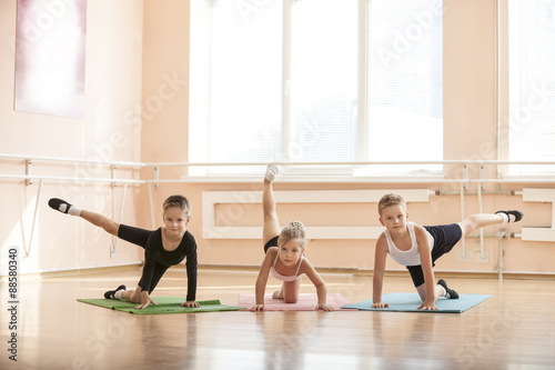 Poster, Tablou Young dancers warming up at ballet class