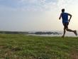 Zdjęcia na płótnie, fototapety, obrazy : Runner on grassy cliff top trail with sea in background