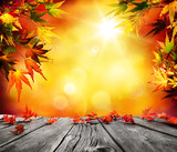 Fototapety Autumn background with red falling leaves on wooden plank