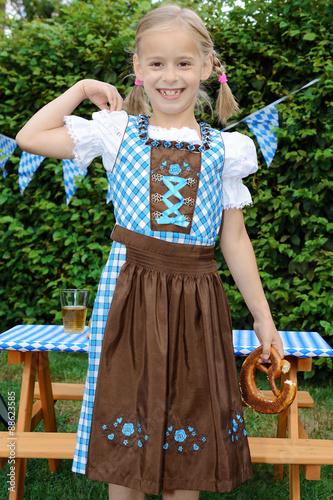 Photo: Mädchen in Dirndl als Trachtenkleid isst Laugenbrezel zum Oktoberfest