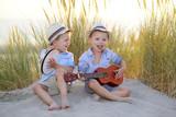 kinderen spelen muziek in de duinen aan zee op vakantie