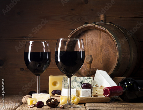 Red wine with various types of cheese on wooden background © nikilitov